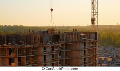 Building site at sunset. A brigade of workers is pouring concrete