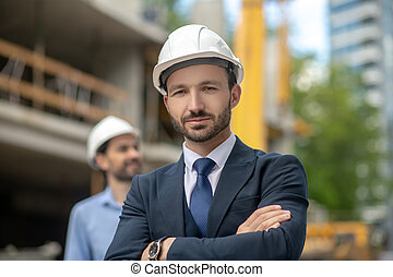 Building supervisor standing with folded arms, foreman looking sideways behind him