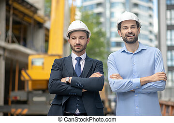 Foreman and building supervisor standing with folded arms on the building site