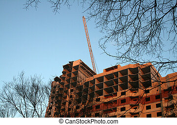 Building site and hoisting crane on background with blue sky...