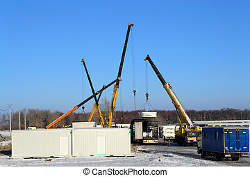 Building site with crane trucks that unloads trucks and...