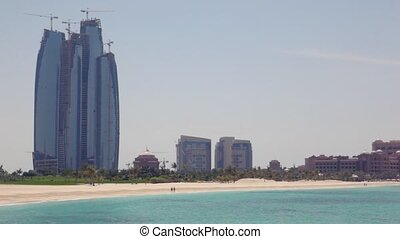 building skyscraper near seashore with palms in Abu Dhabi, UAE