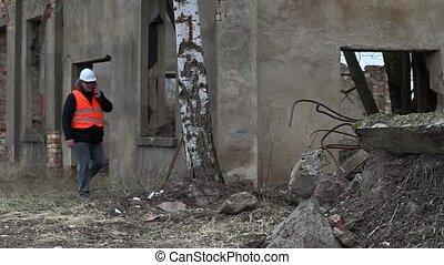 Building supervisor talking on smartphone near abandoned...
