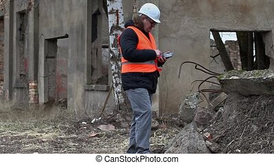 Building supervisor using tablet PC on buildings territory...