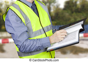 Building surveyor in hi vis checking data and making notes in his site folder