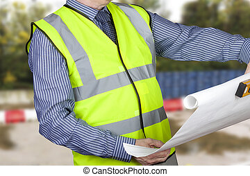 Building surveyor in hi vis checking site plans holding spirit level