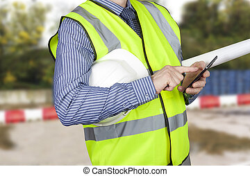 Building surveyor in hi vis with site plans checking his smart phone