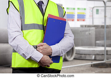 Building surveyor in high visibility carrying clipboard on site