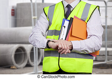 Building surveyor in high visibility checking the time on site