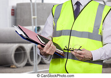 Building surveyor in high visibility vest carrying work folders on site