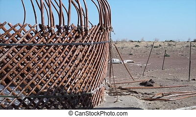 Building the framework of a yurt - A medium shot of a local ...