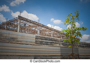 Building under construction in the site surrounded with zinc fence with blue sky background.