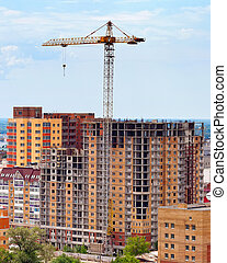Building under construction with crane over blue sky background
