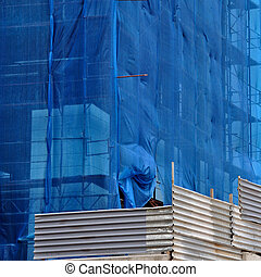building under debris netting at construction site - ...
