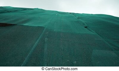 Building under reconstruction covered with green safety nets waving in the wind