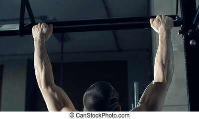 Building Up Muscles - Rear view of athlete pulling up and...
