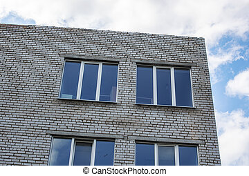Building windows on blue cloudy sky background