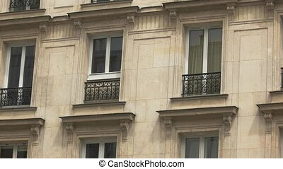 Building with beige walls. Flowers on balcony. Hotel in...