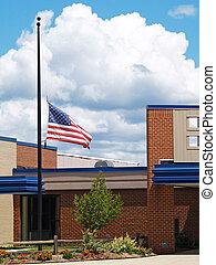 building with flag half mast - a flag flying half mast over ...