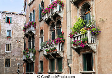 Building with flower boxes on the balconies in a narrow canal, Venice, Italy