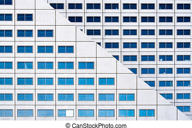 Building with many windows with reflections, Many windows on the facade of the building. Appealing to a little person for attention