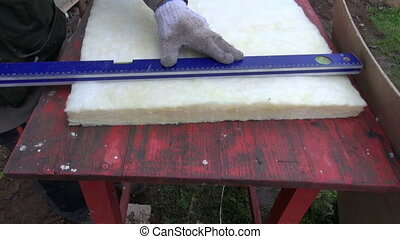 cut mineral rockwool material - building worker cut mineral...