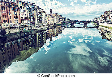 Buildings and Ponte Santa Trinita mirrored in river Arno,...