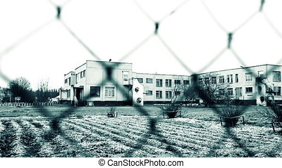 Buildings behind a fence camera switches focus. Black and...