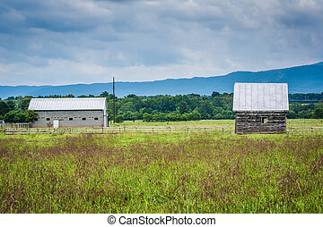 Buildings in a farm field and distant mountains in the rural Shenandoah Valley of Virginia.