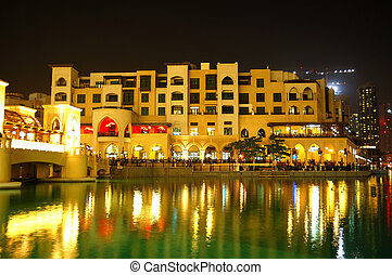 Buildings in Dubai Downtown and man-made lake in night illumination, UAE