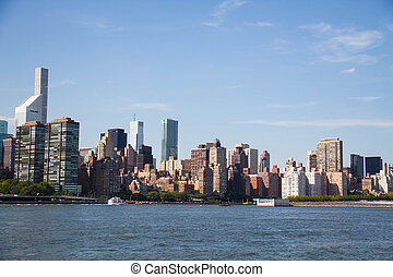 Buildings in Manhattan and the river with blue sky, New York