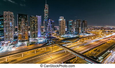 Buildings of Jumeirah Lakes Towers with traffic on the road night timelapse.