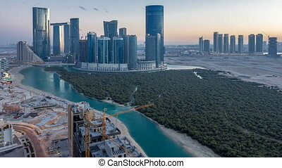 Buildings on Al Reem island in Abu Dhabi day to night...