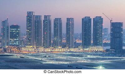 Buildings on Al Reem island in Abu Dhabi day to night...