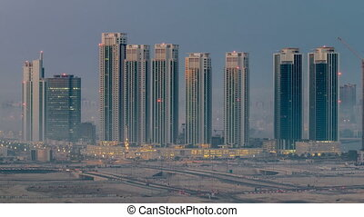 Buildings on Al Reem island in Abu Dhabi night to day timelapse from above.