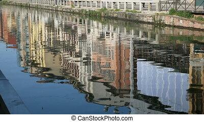 Buildings reflect in the Naviglio grande in Milan
