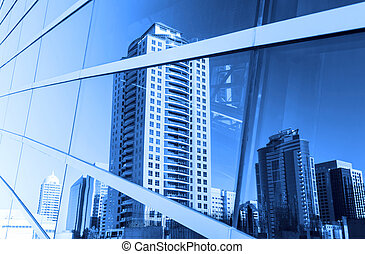 Buildings reflected in windows of office building -...