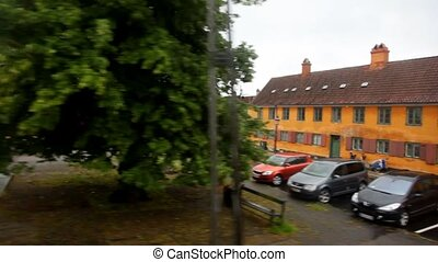 buildings, roads which is flying by behind window of train -...
