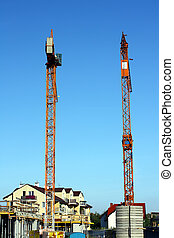 Two cranes in building site