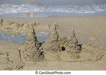 Built House sand castle with towers on the south shore of the sandy beach blue sea.