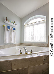 Built in bathtub at the corner of a bathroom with a large arched window