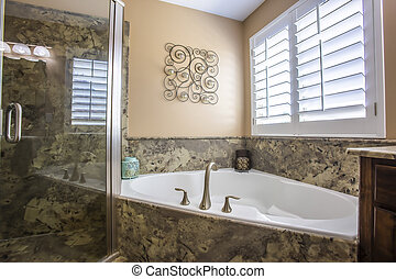 Built in bathtub at the corner of a bathroom with wall decor and window