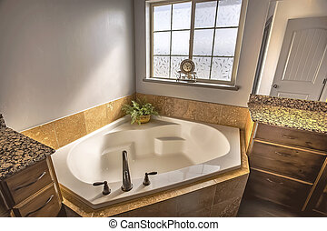 Built in bathtub at the corner of a sunlit bathroom with frosted glass window