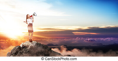 Buiness woman with loudspeaker stands on the top of the mountain.