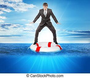 Buisnessman on lifebuoy looking down in sea, balance concept