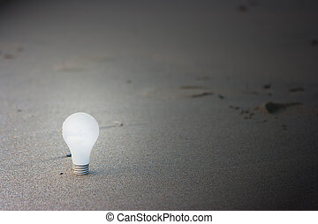 Bulb - White light bulb standing on sand beach
