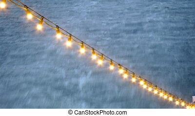 Bulbs garland in front of dark sea, time lapse