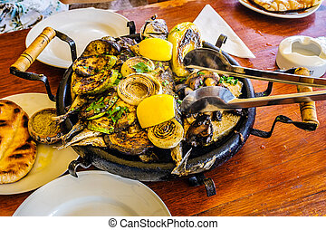 Bulgarian hot plate with fish, courgettes and onions -...
