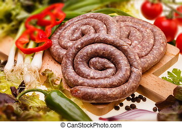 Bulgarian, raw sausages with vegetables on wooden board