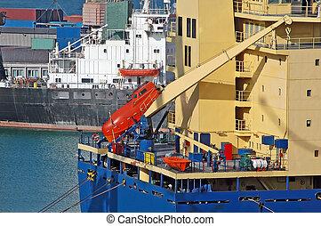 Bulk cargo ship in harbor with pinnace